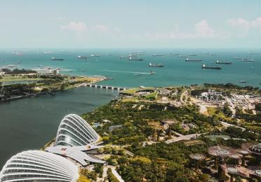 Aerial shot of ships and buildings near ocean in Singapore